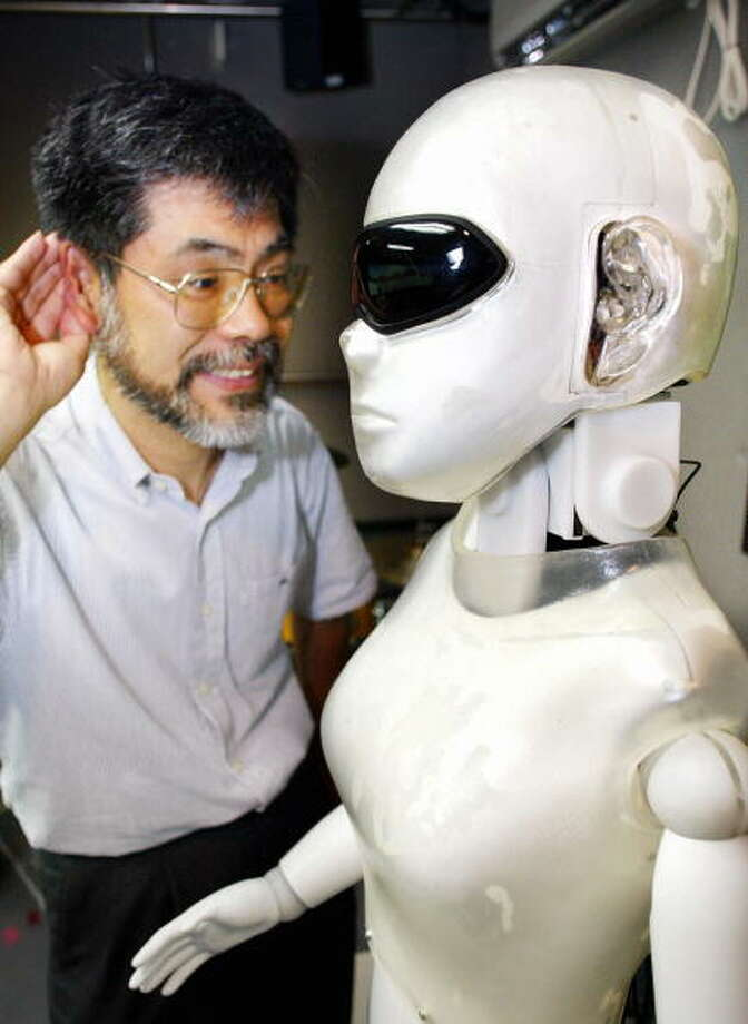 "Kyoto University professor Hiroshi Okuno operates his humanoid robot with silicone made ears ""SIG-II"" which enables to differentiate three mixture human voices when three persons speak at the same time and also gives attention to the direction of human voice with robot's two CCD eyes at his laboratory in Kyoto University 30 June 2003. Professor Okuno researches a real-time auditory and visual tracking system of multiple objects for humanoid robot under real-world environments.    AFP PHOTO / Yoshikazu TSUNO Photo: YOSHIKAZU TSUNO, Getty / 2003 AFP"