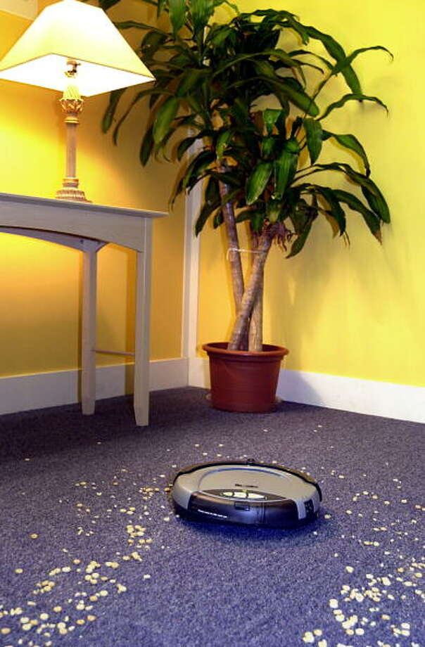 iRobot's Roomba (TM) Intelligent FloorVac - billed as the first automatic floor cleaner in the U.S., is demonstrated at the company headquarters September 25, 2002 in Somerville, Massachusets.  Roomba's unique advanced navigation technology allows it to clean all hosehold floor serfaces, including carpet, tile, wood and linoleum. The Roomba Inteligent FloorVac is available for $199, at Brookstone, The Sharper Image and Hammacher Schlemmer. iRobot has been building and developing advanced robotic systems for the U.S. Department of Defense, the military, law enforcement, energy, cleaning and toy industries for the past 12 years. Photo: Doug McFadd, Getty / 2002 Getty Images