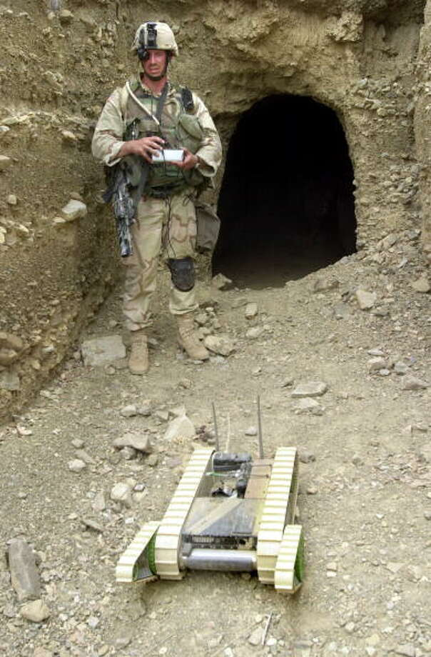 "A U.S. army soldier maneuvers ""Hermes"" the robot into a cave to detect for mines, traps, and other unexploded ordinance as well as weapons or equipment possibly hidden by Taliban or al-Qaeda fugitives July 29, 2002in the eastern border town of Qiqay, Afghanistan. The current war in Afghanistan marks the first time robots have been deployed by conventional forces. Photo: Pool, Getty / 2002 Getty Images"