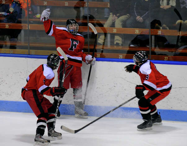 Fairfield Warde/Ludlowe Mustang's #11 Kevin Robinson, arm raised, celebrates a goal against East Catholic, during CIAC Division II boys hocksey state final action at Ingalls Rink in New Haven, Conn. on Wednesday March 20 2013. Photo: Christian Abraham / Connecticut Post