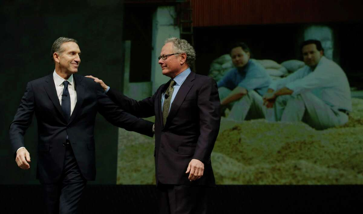 Starbucks CEO Howard Schultz, left, greets retiring longtime Starbucks executive Dave Olsen, right, in front of a 1992 photo of the two of them on a coffee farm in Guatemala, during Starbucks' annual shareholders meeting, Wednesday, March 20, 2013, in Seattle.