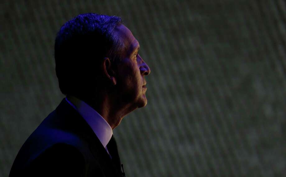 Starbucks CEO Howard Schultz is illuminated by a video screen as he views a presentation at the company's annual shareholders meeting, Wednesday, March 20, 2013, in Seattle, Wash. Photo: Ted S. Warren / Associated Press