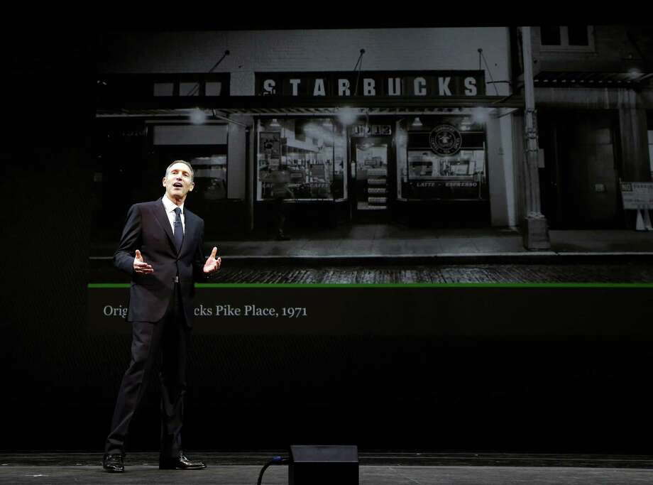 Starbucks CEO Howard Schultz speaks in front of a photo of the first-ever Starbucks store, which is still open at Seattle's Pike Place Market, during the company's annual shareholders meeting, Wednesday, March 20, 2013, in Seattle. Photo: Ted S. Warren / Associated Press