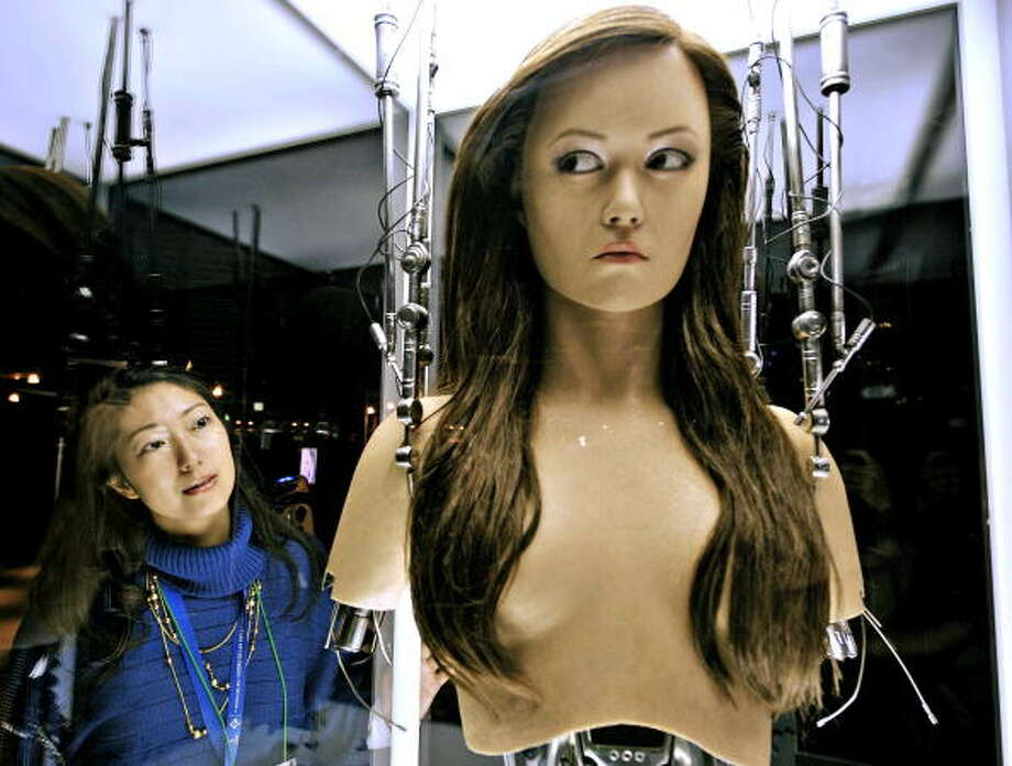 "A woman watches a full-scale figure of a terminator robot ""Cameron Phillipes"" at a preview of the Terminator Exhibition in Tokyo in 2009. The exhibition, displayed figures, properties and movie set of Terminator series, will open March 19 through June 28 as the new movie ""Terminator 4"" will be screning here in June.   AFP PHOTO / Yoshikazu TSUNO Photo: YOSHIKAZU TSUNO, Getty / 2009 AFP"