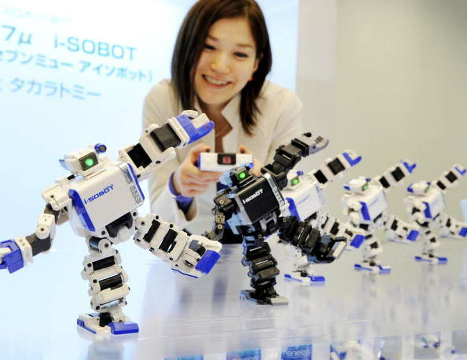 "Chie Yamada, and employee of Japan's toy giant Tomy displays the world's smallest humanoid robot ""i-Sobot"", which is 165mm in height, weighing 350g and equipped with 17 micro actuators and a gyro-sensor as it dances in Tokyo on December 18, 2008. The i-Sobot received the government sposored robot award for this year in Tokyo on December 18.    AFP PHOTO / Yoshikazu TSUNO Photo: YOSHIKAZU TSUNO, Getty / 2008 AFP"