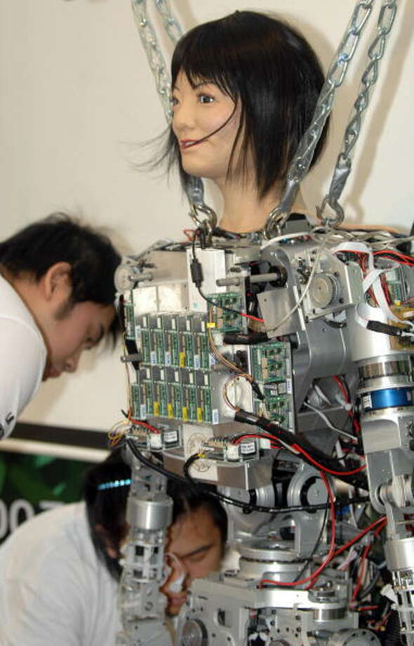 Technicians from a Taiwan university adjust a robot in preparations for the opening of a four-day invention exhibition in Taipei, 27 September 2007. Hundreds of invented items from Taiwan and elsewhere around the world will be on display during the event.   AFP PHOTO/Sam YEH Photo: SAM YEH, Getty / 2007 AFP