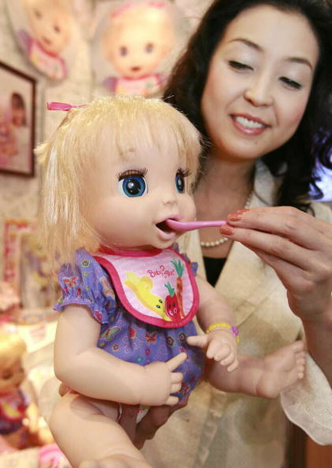 "Japan's toy maker Sega Toys employee, Mineko Sakanoue, displays a baby robot ""Meno"" which is able to blink eyes, move mouth like munching and cry to ask changing its nappy after drinking water at the annual Tokyo Toy Show, 01 July 2007. Sega Toys will put it on the market in November.  AFP PHOTO / Yoshikazu TSUNO Photo: YOSHIKAZU TSUNO, Getty / 2007 AFP"