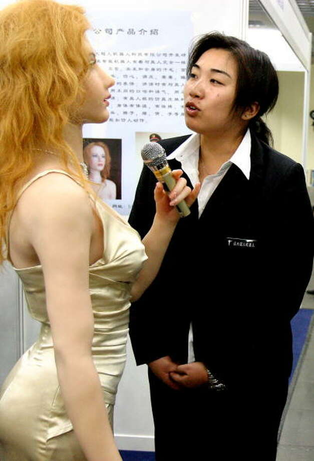"A woman talks with an ""intelligent beauty robot"" displayed at the ongoing 2006 International Conference on Intelligent Robots and Systems on October 11, 2006 at the International Convention Center in Beijing, China. Photo: ChinaFotoPress, Getty / 2006 ChinaFotoPress"