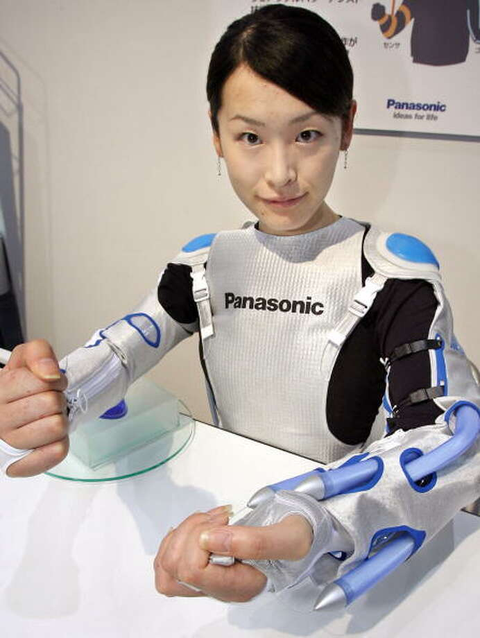 "Japanese electronics giant Matsushita Electric Industrial unveils the prototype model for a ""power jacket"" to help patients recover from partial paralysis during rehabilitation, at the Home Care and Rehabilitation Exhibition in Tokyo, 27 September 2006. The robot jacket, weighing only 1.8 kgs (4 lbs.), has eight artificial muscles powered by compressed air and controlled by four sensors at the elbow and wrist (two each). The sensors are attached to healthy arms and controls the artificial muscles simultaneously on the paralysed side.       AFP PHOTO/YOSHIKAZU TSUNO Photo: YOSHIKAZU TSUNO, Getty / 2006 AFP"