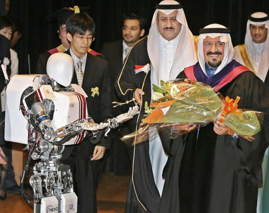 "Saudi Arabian Crown Prince Sultan Bin Abdul Aziz (R) receives a bouquet of flowers from humanoid robot ""Wabian II"" buit by the Waseda University during his honorary doctorate conferral ceremony in Tokyo, 07 April 2006.  The Crown Prince is on a three-day visit to Tokyo. AFP PHOTO/Kazuhiro NOGI Photo: KAZUHIRO NOGI, Getty / 2006 AFP"