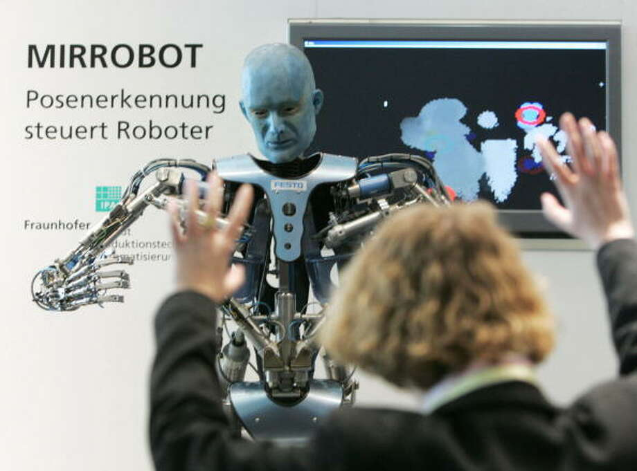 "The Festo ""Tron-X"" robot mimics the gestures of a fair-goer (front) at the stand of the Fraunhofer Institute for Production Technology and Automatisation during the 2006 CeBIT information and telecommunication technology fair 14 March 2006 in Hanover. The robot analyses human gestures thanks to a 3-D camera sensor, and then reproduces them. The world's biggest IT fair runs to 15 March, and some 6300 exhibitors of 71 countries present their products. AFP PHOTO JOHN MACDOUGALL Photo: JOHN MACDOUGALL, Getty / 2006 AFP"