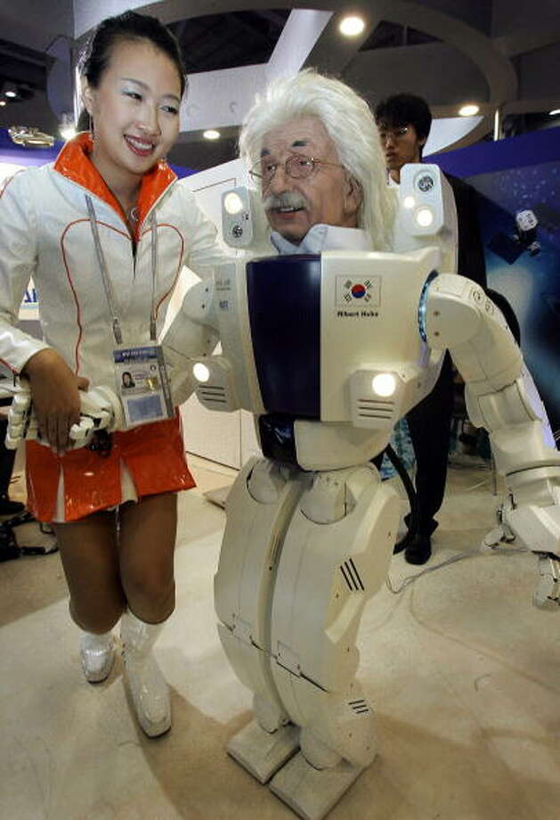 "A model shakes hands with a multi-directional robot ""Albert Hubo"" at an Information Technology exhibition on the sidelines of the Asia-Pacific Economic Cooperation (APEC) forum in Busan, 15 November 2005.     AFP PHOTO/MIKE CLARKE Photo: MIKE CLARKE, Getty / 2005 AFP"