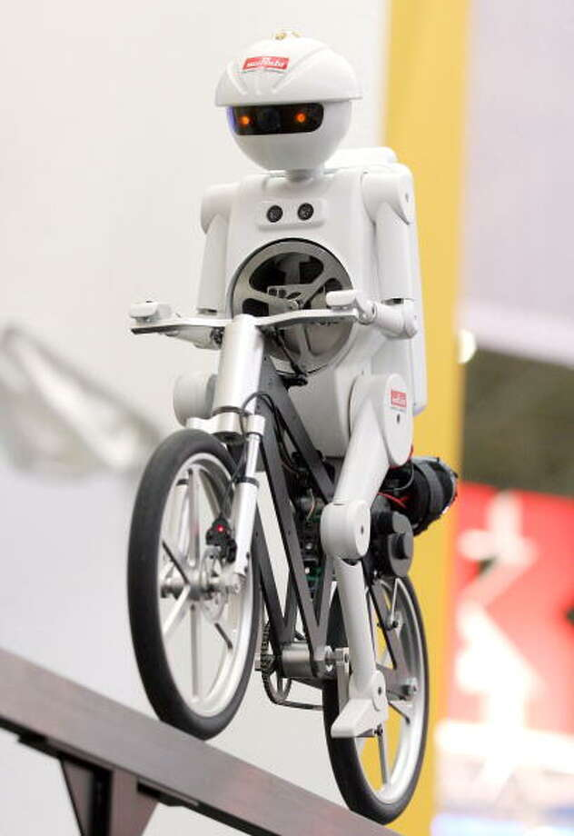"Murata Manufacturing Co. Ltd's bicycling robot 'Murataseisaku-kun' or 'Murata Boy' is seen in action during the Asia's electronics trade show CEATEC on on October 4, 2005 in Chiba, Japan. ""Murataseisaku-kun"" can run at any speed from 0 to approximately 60cm/sec without falling, can stand still without falling and it can also run backwards. Photo: Junko Kimura, Getty / 2005 Getty Images"
