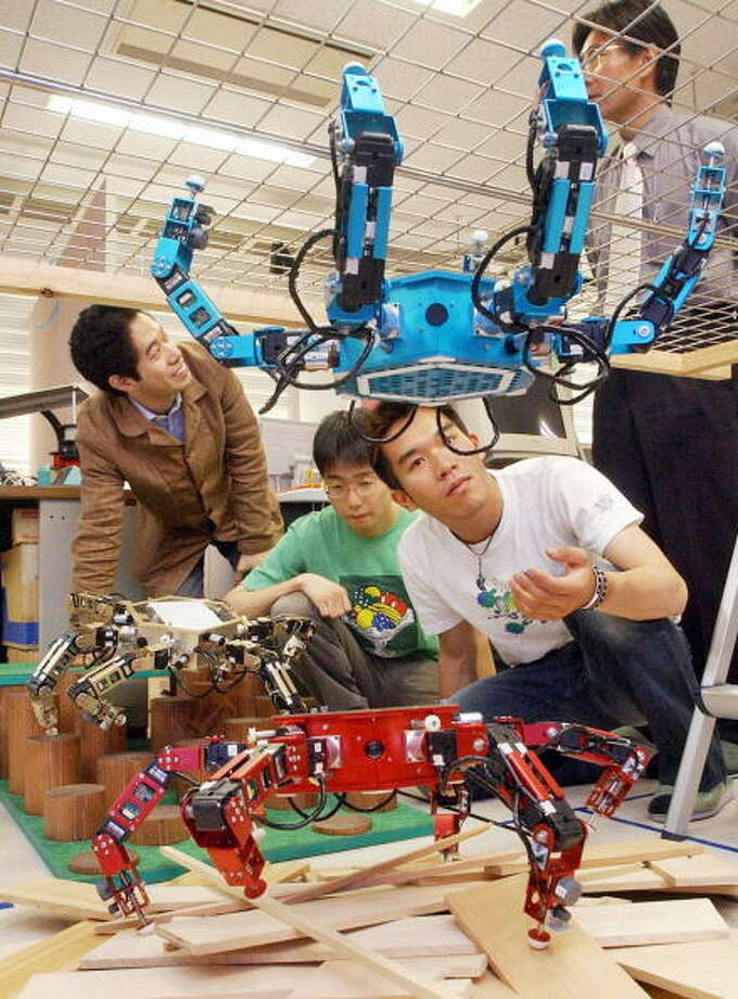 "Students of Japan's Osaka University operate spider shaped robots ""Asterisk"", developped by Professor Tatsuo Arai, at Arai's laboratory in Osaka, 06 June 2005.  The robot, able to progress through hazardous grounds and even up side down, will be displayed at the 2005 World Expo Aichi from 09 June.   AFP PHOTO/JIJI PRESS Photo: AFP, Getty / 2005 AFP"