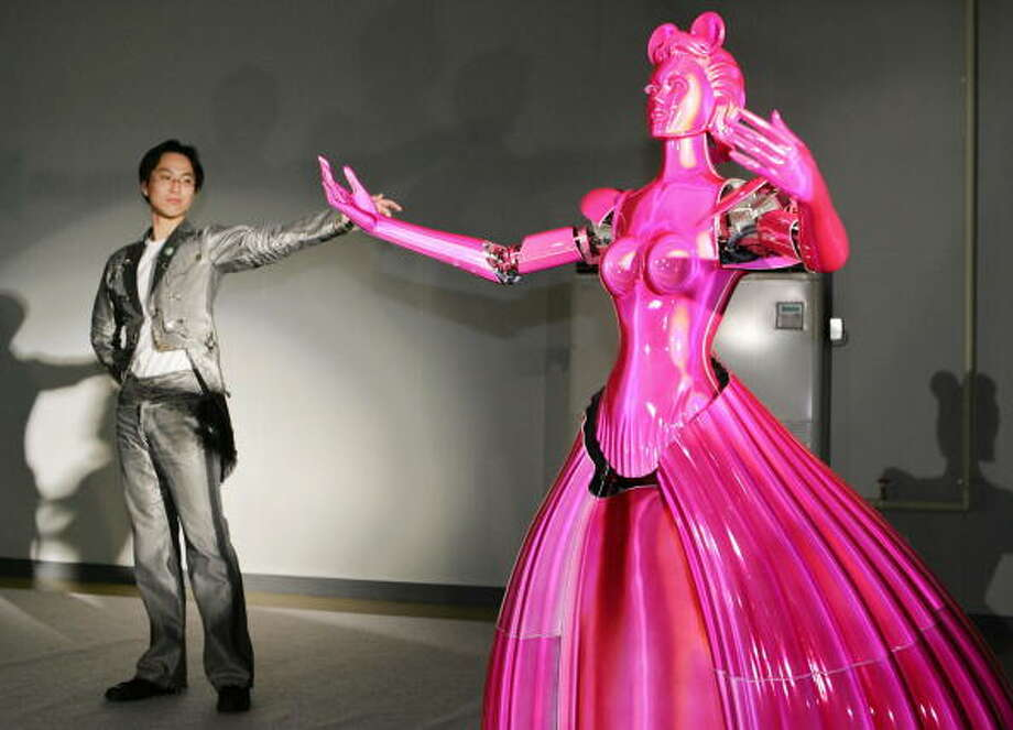 Takahiro Takeda, postgraduate student of Japan's Tohoku Univ. dances with Partner Ballroom Dance Robot (PBDR) at a factory of Nomura Unison robotic venture company in Chino city, 200-km west of Toyko 04 June 2005.  The prototype dance partner robot, developped by Japan's Tohoku Univ Professor Kazuhiro Kosuge, enables them to move in all directions with three special wheels by predicting how its partner will mobe with a sensor. The robot will be displayed at the World Expo Aichi 2005 from 09 June.    AFP PHOTO / Yoshikazu TSUNO Photo: YOSHIKAZU TSUNO, Getty / 2005 AFP