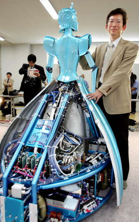 Dr. Kazuhiro Kosuge, Professor of Japan's Tohoku Univ. unveils the Partner Ballroom Dance Robot (PBDR) at a factory of Nomura Unison robotic venture company in Chino city, 200-km west of Toyko 04 June 2005.  The prototype dance partner robot, developped by Japan's Tohoku Univ Professor Kazuhiro Kosuge, enables them to move in all directions with three special wheels by predicting how its partner will mobe with a sensor. The robot will be displayed at the World Expo Aichi 2005 from 09 June.    AFP PHOTO / Yoshikazu TSUNO Photo: YOSHIKAZU TSUNO, Getty / 2005 AFP