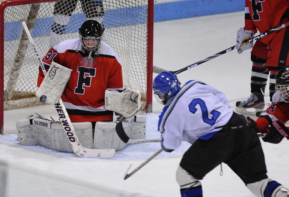 Fairfield Warde/Ludlowe Mustang goalie Kyle Greenhut tries to block a shot by East Catholic's #2 Brian O'Connell, during CIAC Division II boys hocksey state final action at Ingalls Rink in New Haven, Conn. on Wednesday March 20 2013. O'Connell scored on this attempt. Photo: Christian Abraham / Connecticut Post