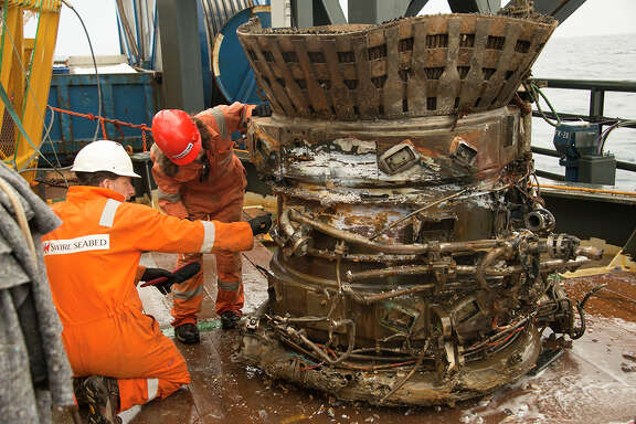 Workers inspect a thrust chamber of an Apollo F-1 engine recovered from the Atlantic Ocean.
