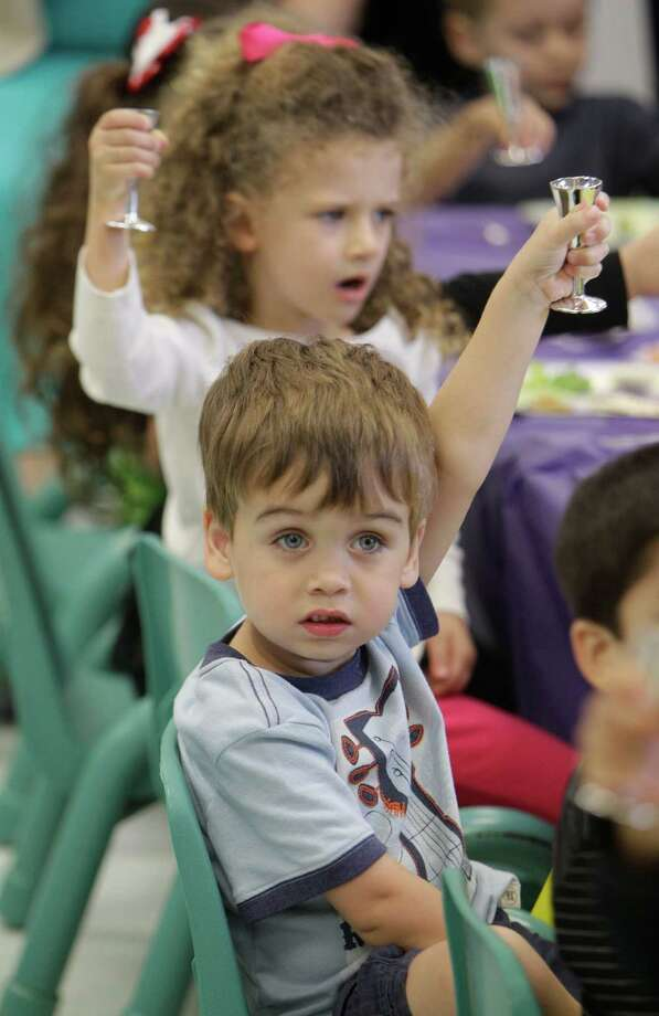 Three-year-olds Colby Stewart, front, and Avery Fisher raise a glass of grape juice that symbolizes wine as preschool students participate in a Passover Seder. Photo: Melissa Phillip, Houston Chronicle / © 2013  Houston Chronicle