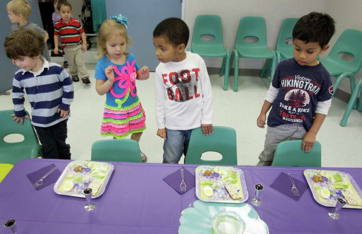 Simon Zamberk, left, Hannah Tomlinson, Patrick Jones and Ishan Narkar, right, look for a seat as they participate in a Passover Seder.