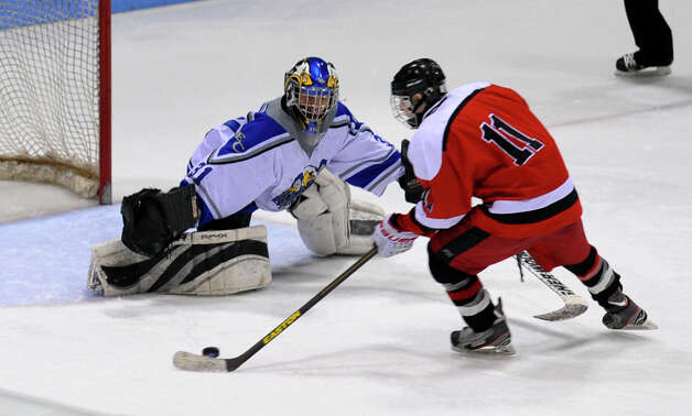 Fairfield Warde/Ludlowe Mustang's #11 Kevin Robinson manuevers the puck for a penalty goal shot past East Catholic goalie Thomas Usseglio, during fourth period overtime of CIAC Division II boys hocksey state final action at Ingalls Rink in New Haven, Conn. on Wednesday March 20 2013. Robinson made the shot giving Fairfield the win. Photo: Christian Abraham / Connecticut Post