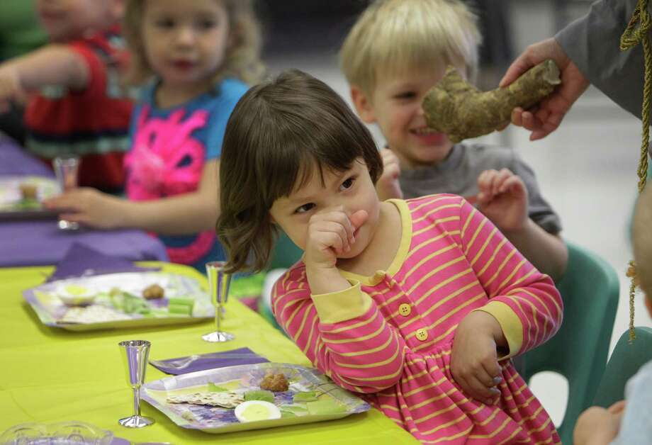 Grace Germany reacts to smelling horseradish as a group of three-year-old preschool students at Bertha Alyce Early Childhood Center  participate in a Passover Seder. Photo: Melissa Phillip, Houston Chronicle / © 2013  Houston Chronicle