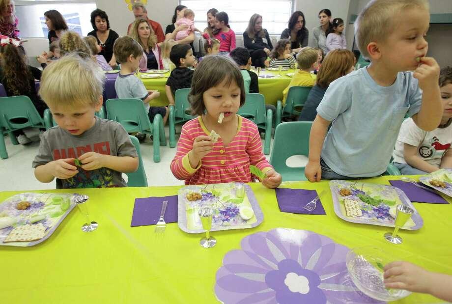 Henry Rorai, left, Grace Germany, center, and Declan Garrett, right, take part in a Passover Seder. Photo: Melissa Phillip, Houston Chronicle / © 2013  Houston Chronicle