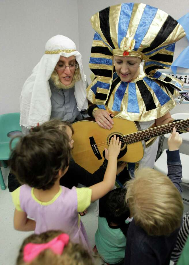 Alana Shepetofsky, left, curriculum coordinator, portrays Moses and Cathy Shelley, music director, portrays King Pharaoh for a group of three-year-old preschool students at Bertha Alyce Early Childhood Center. Photo: Melissa Phillip, Houston Chronicle / © 2013  Houston Chronicle