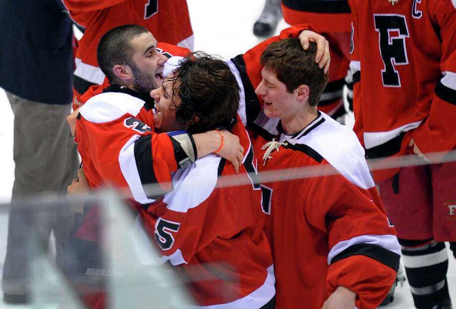 Fairfield Warde/Ludlowe Mustang's #2 Conor Scharlop, left hugs teammates #5 Daniel Silvestri and #1 Connor Frawley, right, after the team defeated East Catholic in fourth period overtime of CIAC Division II boys hocksey state final action at Ingalls Rink in New Haven, Conn. on Wednesday March 20 2013. Robinson made a penatly shot giving Fairfield the win. Photo: Christian Abraham / Connecticut Post
