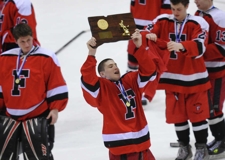 Fairfield Warde/Ludlowe Mustang's #11 Kevin Robinson proudly holds up the CIAC Division II trophy after the team beat East Catholic, during CIAC Division II boys hocksey state final action at Ingalls Rink in New Haven, Conn. on Wednesday March 20 2013. Photo: Christian Abraham / Connecticut Post