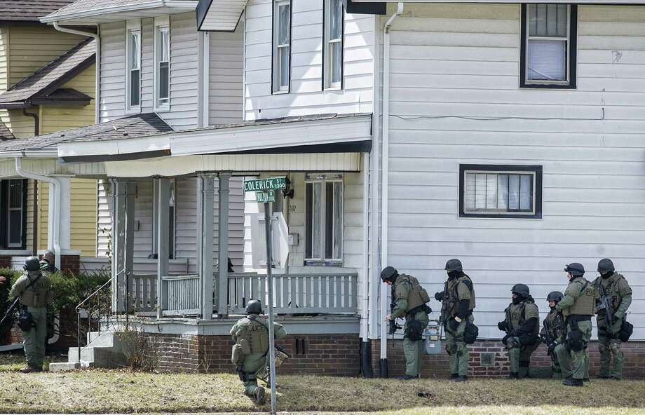 Armed officers surround a house in Fort Wayne, Ind., where police say a man who killed a bus passenger earlier in the day was holding a 3-year-old child hostage. The child was later freed and the gunman shot and killed. Photo: Swikar Patel / Associated Press