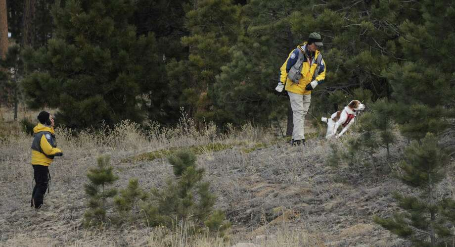 Searchers use a dog to search the area around the Monument, Colo., home of Department of Corrections Executive Director Tom Clements, who was killed in a surprise attack Tuesday night as he answered his front door. Photo: Mark Reis / Associated Press