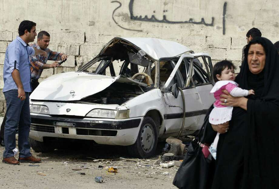 Iraqis inspect damage from a car bomb attack in the Baghdad's Zayona neighborhood. Photo: Hadi Mizban / Associated Press