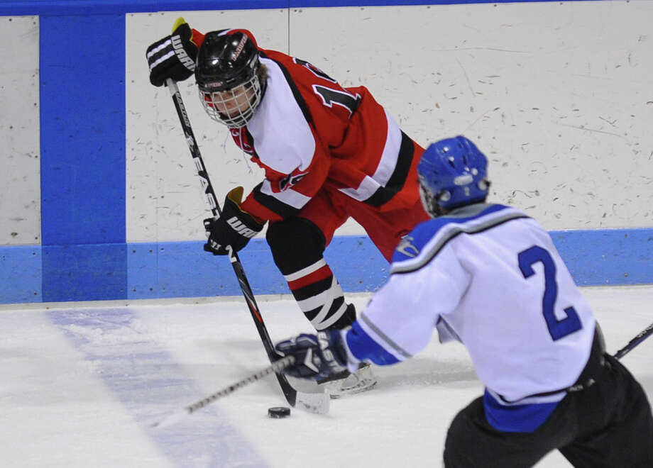 Fairfield Warde/Ludlowe Mustang's #19 Paul Barlow moves the puck as East Catholic's #2 Brian O'Connell chases, during CIAC Division II boys hocksey state final action at Ingalls Rink in New Haven, Conn. on Wednesday March 20 2013. Photo: Christian Abraham / Connecticut Post