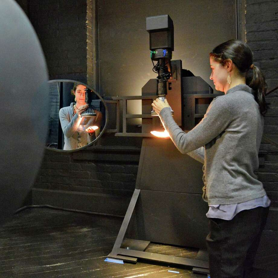 Masters of science and lighting student Erin Ryan prepares an LED lamp for measurement in  RPI 's new photometry lab adjusts LED's inside a 2 meter integrating sphere at their Lighting Research Center in Troy Wednesday March 20, 2013.  (John Carl D'Annibale / Times Union) Photo: John Carl D'Annibale