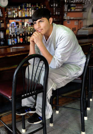 Jose Minchala, 21, of Danbury, came to the United States from Ecuador as a small child.  He spends much of his free time at the Ecuadorean restaurant, El Milenio on North Street in Danbury, Conn. where he is photographed, Wednesday, March 20, 2013. Photo: Carol Kaliff / The News-Times