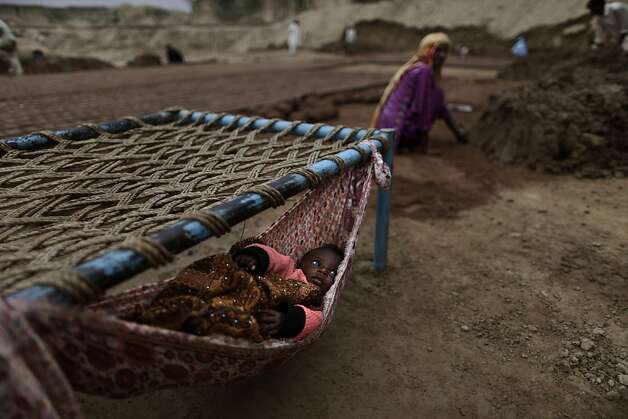 A Pakistani child, lies in a hammock as her mother makes bricks, at a brick factory in Mandra, near Rawalpindi, Pakistan, Wednesday, March 20, 2013. (AP Photo/Muhammed Muheisen) Photo: Muhammed Muheisen, Associated Press
