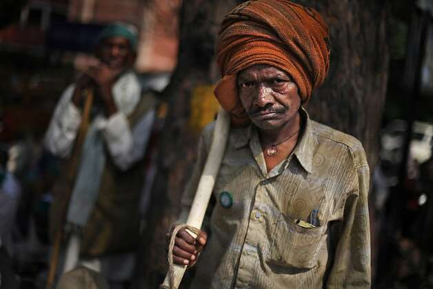 An Indian farmer, armed with a stick, reacts to the camera as he listens to a speaker, unseen, during a protest near the Indian Parliament in New Delhi, India, Wednesday, March 20, 2013. The farmers were protesting against government procuring land for setting up industry and not providing enough subsidy to farmers among several other grievances. (AP Photo/Altaf Qadri) Photo: Altaf Qadri, Associated Press