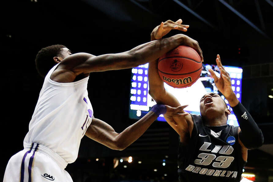 DAYTON, OH - MARCH 20:  E.J. Reed #33 of the LIU Brooklyn Blackbirds goes up against Andre Nation #1