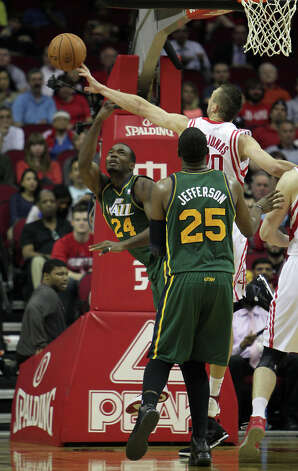 Paul Millsap is fouled by Donatas Motiejunas as Millsap's teammate Al Jefferson looks on. Photo: James Nielsen, Houston Chronicle / © 2013 Houston Chronicle