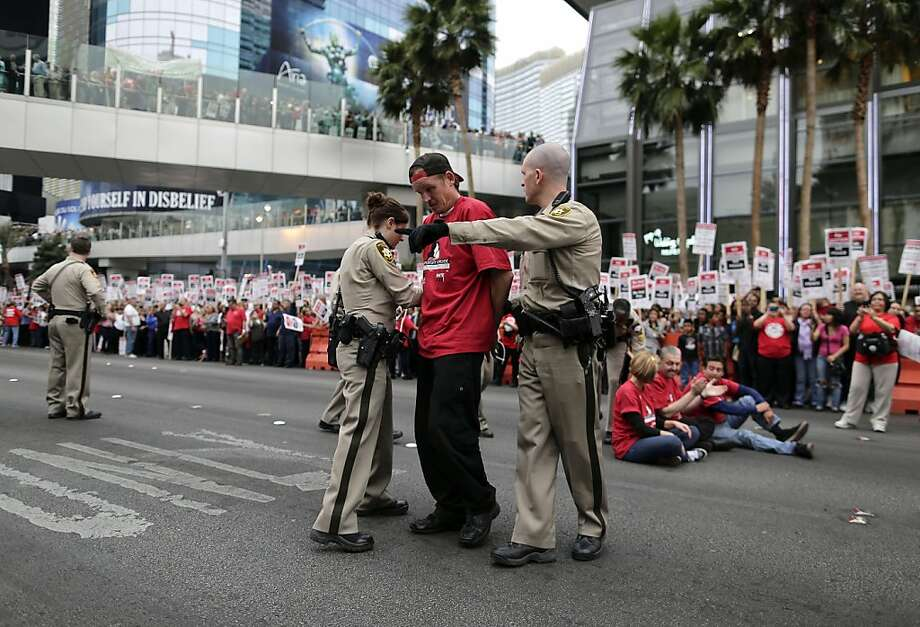 Las Vegas Metropolitan Police officers lead away a protestor during a civil disobedience demonstration by Culinary Union workers outside the Cosmopolitan Hotel-Casino, Wednesday, March 20, 2013, in Las Vegas. Nearly 98 protestors were arrested during the demonstration in which they sat on and blocked traffic along Las Vegas Boulevard. Workers have been in contract talks with Cosmopolitan Las Vegas owner Deutsche  Bank for two years. (AP Photo/Julie Jacobson) Photo: Julie Jacobson, Associated Press