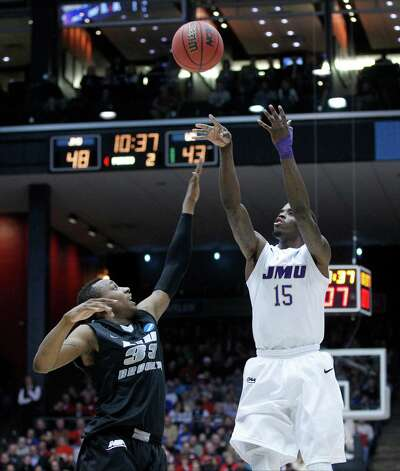 Andre Nation (15) of James Madison is guarded by Kenny Onyechi (33) of LIU Brooklyn. Photo: Barbara J. Perenic, McClatchy-Tribune News Service / Dayton Daily News