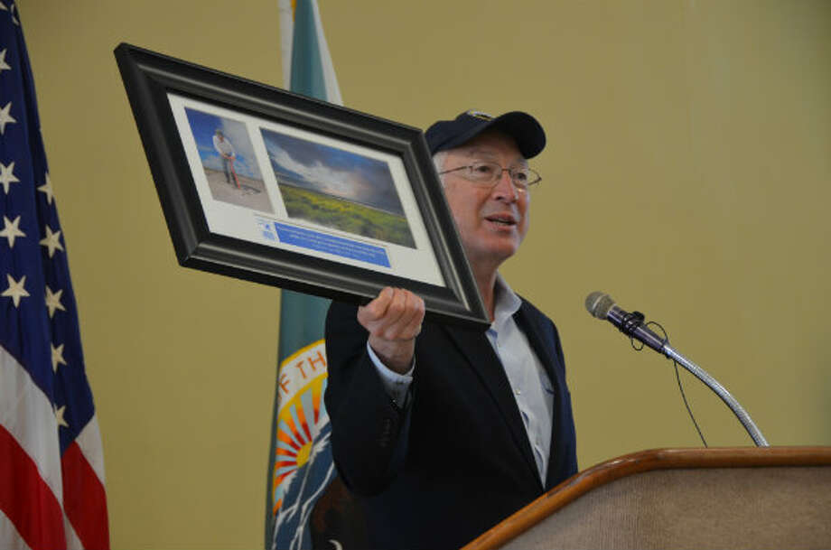 Interior Secretary Ken Salazar hoists a before and after photo of the Big Branch National Wildlife Refuge marsh where he planted oyster grass three years ago, during a meeting with Gulf Coast residents about efforts to restore the region.