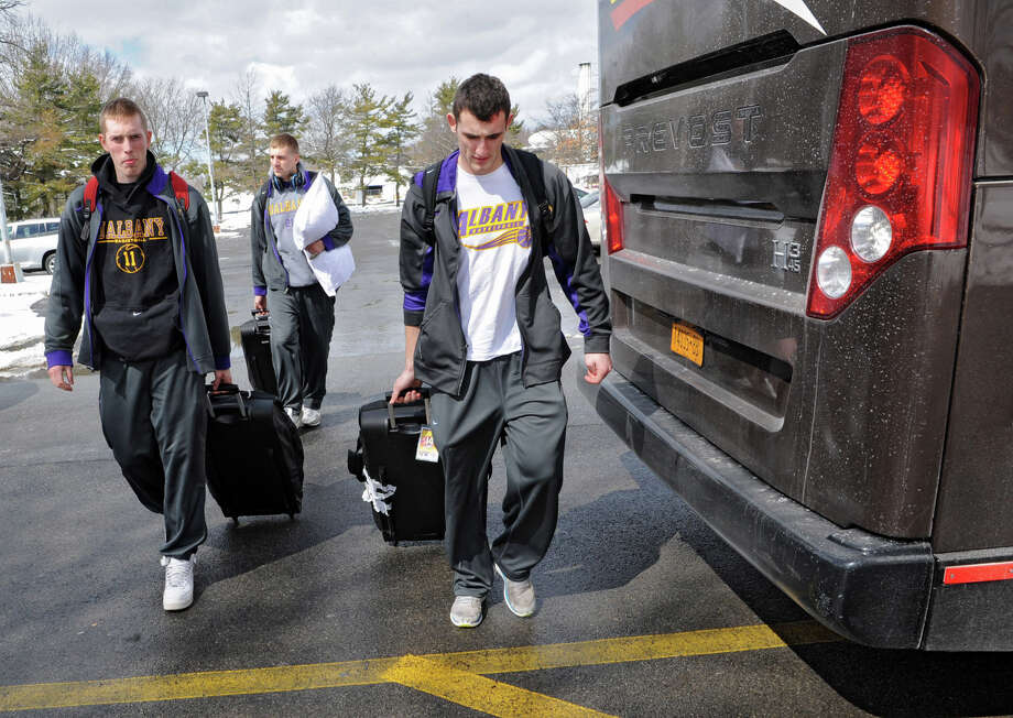 From left, UAlbany basketball players Luke Delvin, Blake Metcalf and Sam Rowley wheel their luggage to the tour bus as the team leaves for the NCAA Tournament on Wednesday, March 20, 2013 in Albany, N.Y. (Lori Van Buren / Times Union) Photo: Lori Van Buren