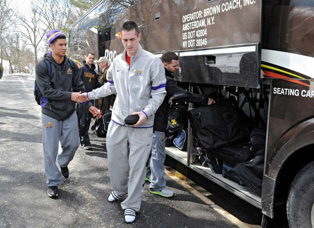"From left, UAlbany basketball player Tanner Gibson gives radio color analyst Zach Bye a ""low five"" before boarding the tour bus as the team leaves for the NCAA Tournament on Wednesday, March 20, 2013 in Albany, N.Y. (Lori Van Buren / Times Union) Photo: Lori Van Buren"