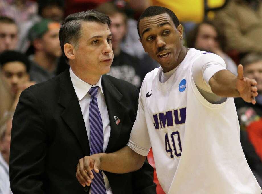 James Madison head coach Matt Brady, left, talks with guard Devon Moore (40) in the second half of a first-round game against LIU Brooklyn in the NCAA college basketball tournament on Wednesday, March 20, 2013, in Dayton, Ohio. (AP Photo/Al Behrman) Photo: Al Behrman