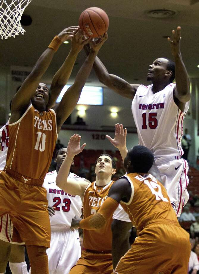 Texas' Jonathan Holmes (left) battles Houston's Leon Gibson (right) and others for a rebound Wednesday night. The Longhorns were knocked out of the CBI with the loss to the Cougars. Photo: J. Patric Schneider / Houston Chronicle