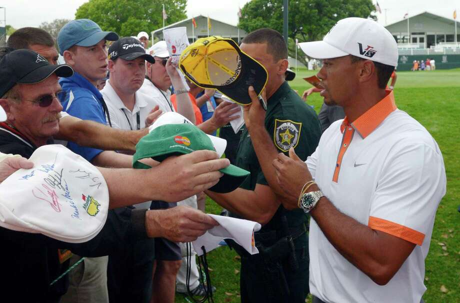 Tiger Woods, right, signs autographs for fans after finishing his weather-shortened round on the ninth green of the pro-am of the Arnold Palmer Invitational golf tournament in Orlando, Fla., Wednesday, March 20, 2013.(AP Photo/Phelan M. Ebenhack) Photo: Phelan M. Ebenhack