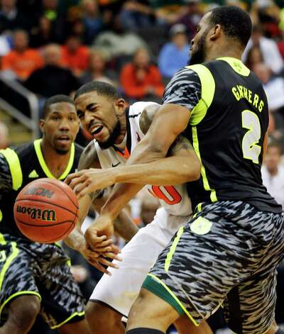 FILE - This March 14, 2013 file photo shows Oklahoma State forward Michael Cobbins (20) as he is fouled by Baylor forward Rico Gathers (2) during the second half of an NCAA college basketball game in the Big 12 tournament in Kansas City, Mo. Oklahoma State won 74-72. The neon-colored jerseys and camouflage-covered shorts debuted by six teams in their post-season conference championships ahead of the NCAA men's basketball tournament weren't well received in the press and social media. The changes happened to be in line with fashion runways and in recreational athleticwear, where highlighter brights and creative camo have been bona fide trends, and alternate uniforms have become part of the college football and basketball landscape, but on the court, these uniforms still made fans cringe. (AP Photo/Orlin Wagner, file) Photo: Orlin Wagner