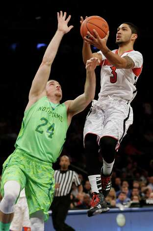FILE - This March 15, 2013 file photo shows Louisville's Peyton Siva (3) driving past Notre Dame's Pat Connaughton (24) during the first half of an NCAA college basketball game at the Big East Conference tournament in New York. The neon-colored jerseys and camouflage-covered shorts debuted by six teams in their post-season conference championships ahead of the NCAA men's basketball tournament weren't well received in the press and social media. The changes happened to be in line with fashion runways and in recreational athleticwear, where highlighter brights and creative camo have been bona fide trends, and alternate uniforms have become part of the college football and basketball landscape, but on the court, these uniforms still made fans cringe. (AP Photo/Frank Franklin II, file) Photo: Frank Franklin II